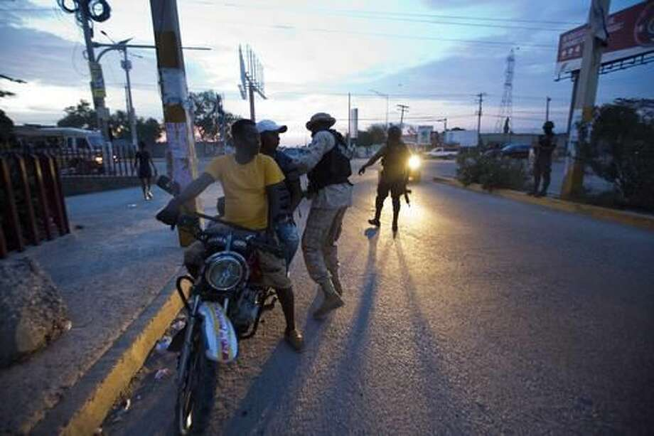 Police check motorists after a jail break at the Civil Prison in the coastal town of Arcahaiea, Haiti, Saturday, Oct. 22, 2016. Over 100 inmates escaped after they overpowered guards who were escorting them to a bathing area. (AP Photo/Dieu Nalio Chery)