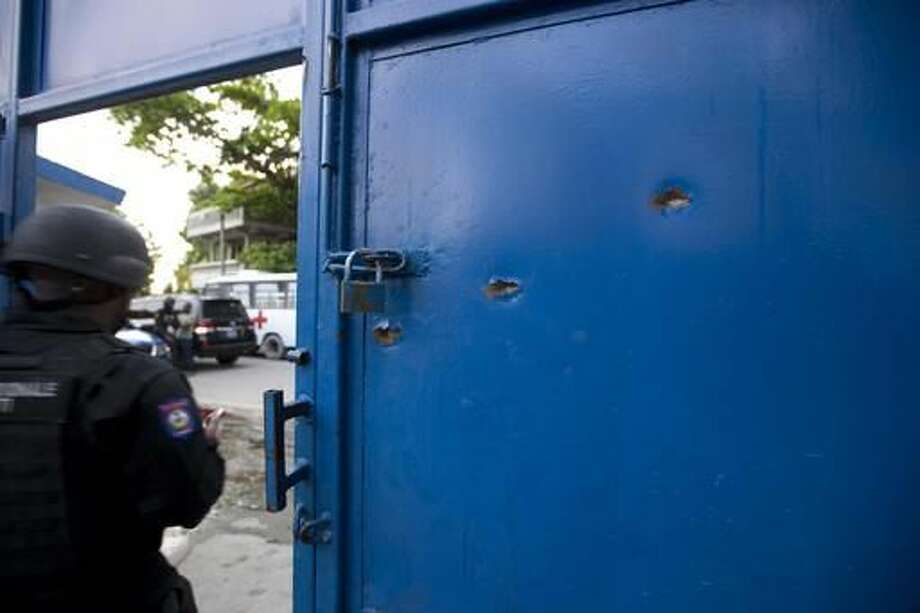 Bullet holes pierce the main gate of the Civil Prison after a jail break in the coastal town of Arcahaiea, Haiti, Saturday, Oct. 22, 2016. Over 100 inmates escaped after they overpowered guards who were escorting them to a bathing area. (AP Photo/Dieu Nalio Chery)