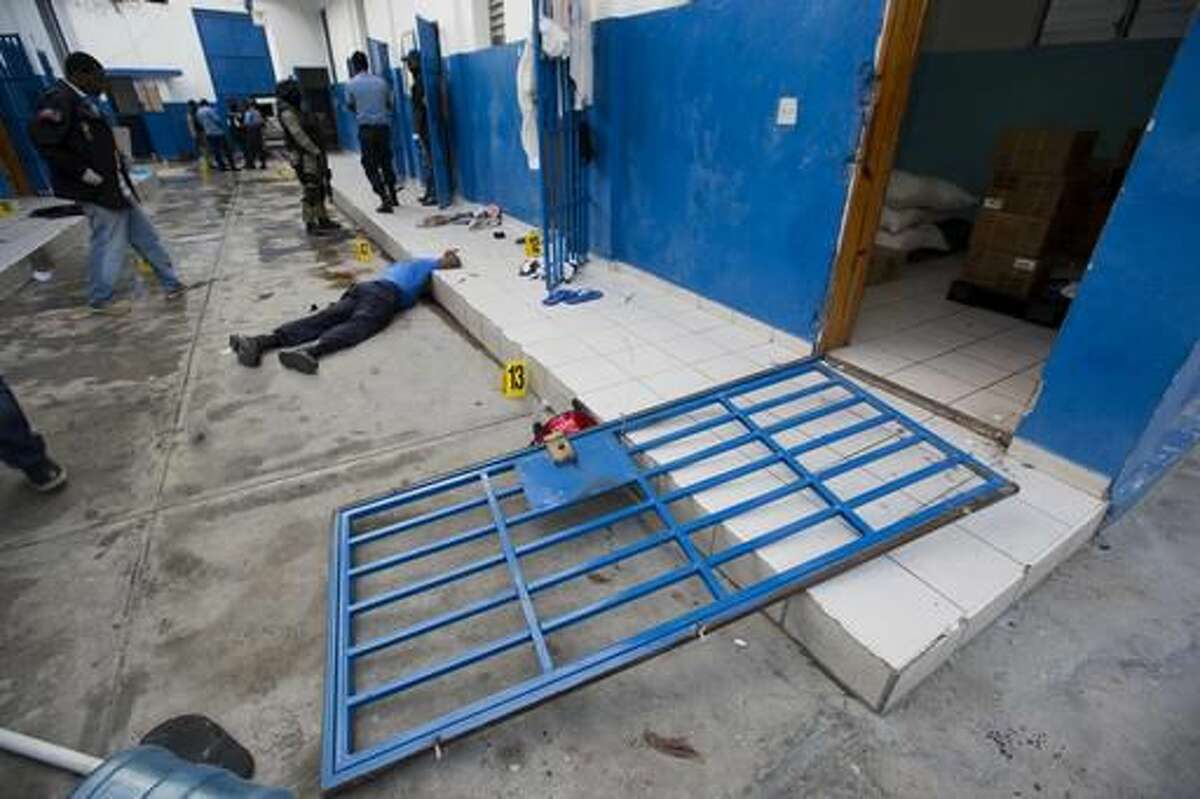A guard lies dead inside the Civil Prison after a jail break in the coastal town of Arcahaiea, Haiti, Saturday, Oct. 22, 2016. Over 100 inmates escaped after they overpowered guards who were escorting them to a bathing area. (AP Photo/Dieu Nalio Chery)