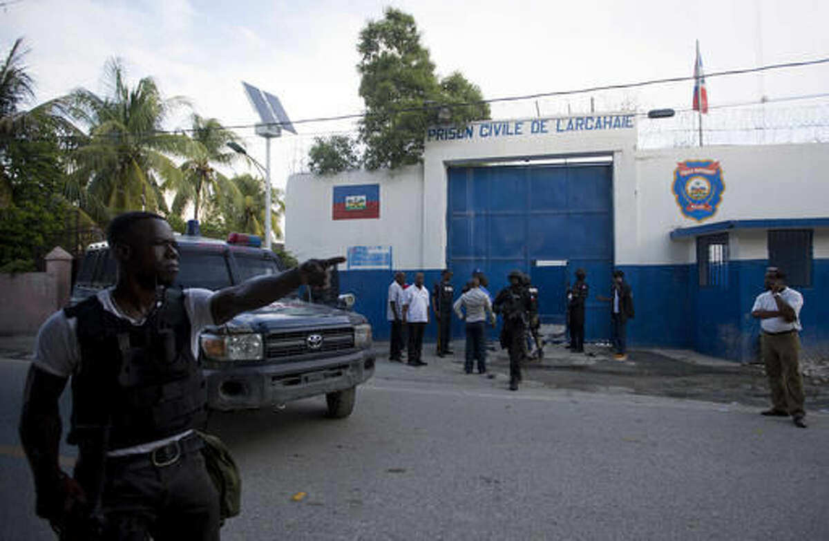 Police gather at the Civil Prison after some inmates escaped in the coastal town of Arcahaiea, Haiti, Saturday, Oct. 22, 2016. Over 100 inmates escaped after they overpowered guards who were escorting them to a bathing area. (AP Photo/Dieu Nalio Chery)