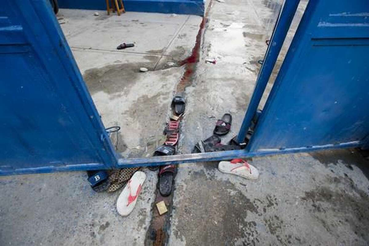 Inmates' sandals lay at the main gate of the Civil Prison in the coastal town of Arcahaiea, Haiti, Saturday, Oct. 22, 2016. Over 100 inmates escaped after they overpowered guards who were escorting them to a bathing area. (AP Photo/Dieu Nalio Chery)