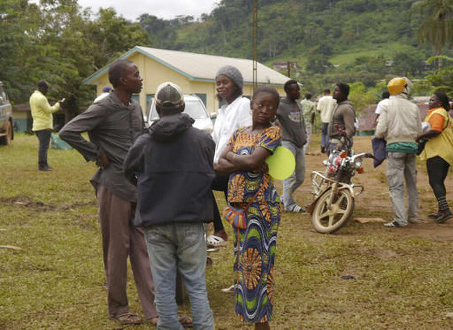 Family members and friends of suspected victims of a train that crashed Friday gather near a morgue, rear, in Eseka, Cameroon, Saturday, Oct. 22, 2016. Rescue workers dug through the rubble Saturday in search of more injured and dead after a train traveling between two major cities in Cameroon derailed in Eseka, killing scores of people according to rescue workers and hospital staff. (AP Photo/Joel Kouam)