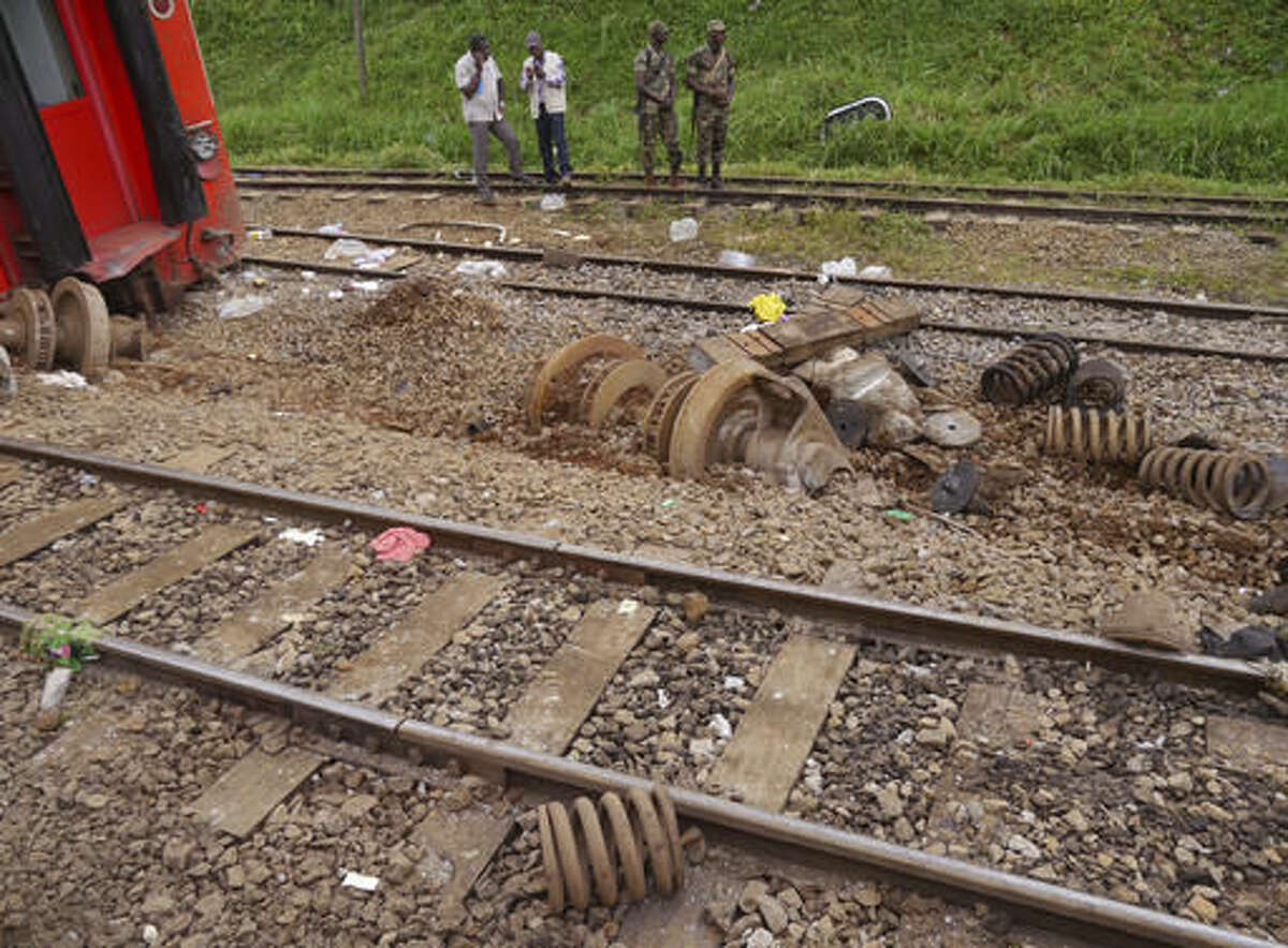 Cameroon soldiers, rear, provide security near train parts from a derailed train in Eseka, Cameroon, Saturday, Oct. 22, 2016. Rescue workers dug through the rubble Saturday in search of more injured and dead after a train traveling between two major cities in Cameroon derailed in Eseka, killing scores of people according to rescue workers and hospital staff. (AP Photo/Joel Kouam)