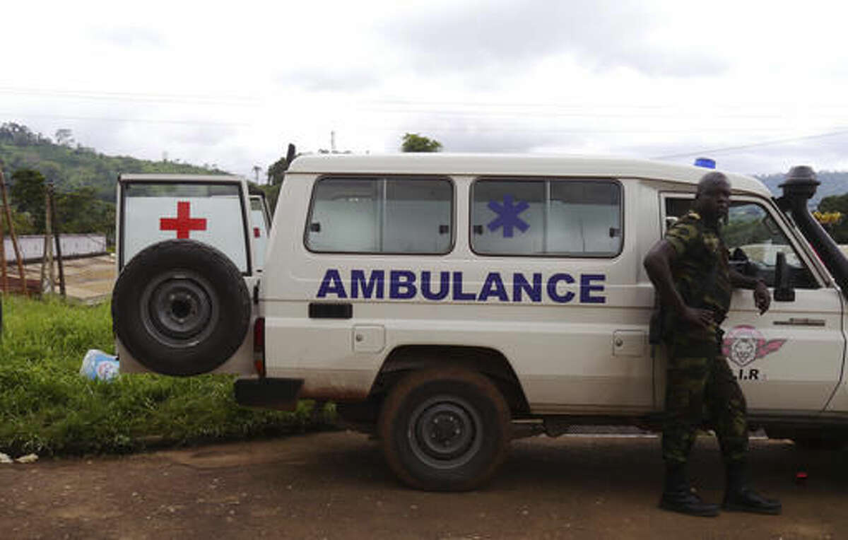 A Cameroon trooper, right, stands next to an ambulance that was used to carry victims of a train that crashed on Friday in Eseka, Cameroon, Saturday, Oct. 22, 2016. Rescue workers dug through the rubble Saturday in search of more injured and dead after a train traveling between two major cities in Cameroon derailed in Eseka, killing scores of people according to rescue workers and hospital staff. (AP Photo/Joel Kouam)