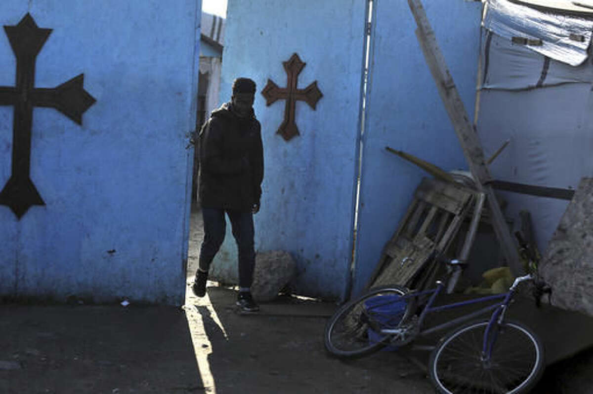 A man leaves the church at a makeshift migrant camp near Calais, France, Sunday, Oct. 23, 2016. Aid workers in the port town of Calais are expressing worry over a lack of information ahead of Monday's scheduled dismantling of France's slum-like migrant camp. French authorities have said they plan to relocate the 6,486 people still staying at the camp to reception centers across the country or abroad as a