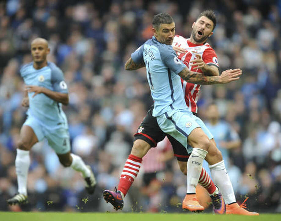 Manchester City's Aleksandar Kolarov tackles Southampton's Charlie Austin, right, during the English Premier League soccer match between Manchester City and Southampton at the Etihad Stadium in Manchester, England, Sunday, Oct. 23, 2016. (AP Photo/Rui Vieira)