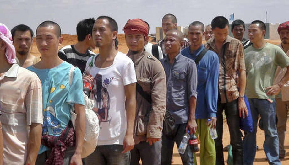 """Sailors who had been held hostage by pirates for more than four years, queue to board an airplane after being released in Galkayo, Somalia Sunday, Oct. 23, 2016. A Somali pirate said Saturday that 26 Asian sailors held hostage for more than four years have been released after a ransom was paid, and international mediators said it """"represents the end of captivity for the last remaining seafarers taken hostage during the height of Somali piracy."""" (AP Photo)"""
