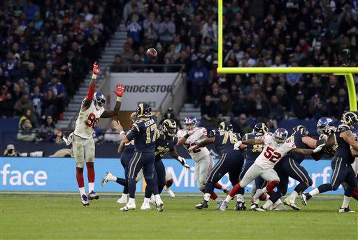 New York Giants defensive end Jason Pierre-Paul (90) attempts to catch during an NFL football game between New York Giants and Los Angeles Rams at Twickenham stadium in London, Sunday Oct. 23, 2016. (AP Photo/Matt Dunham)