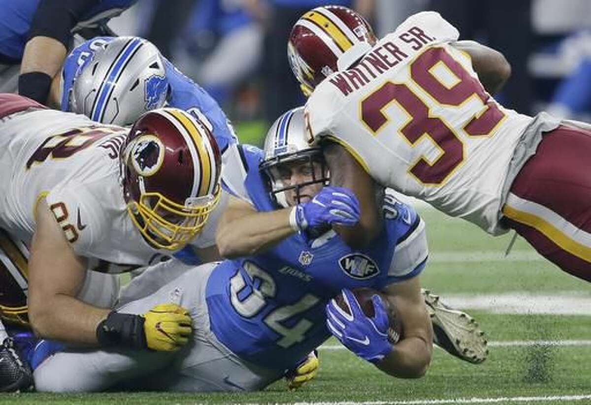 Detroit Lions fullback Zach Zenner (34) is tackled by Washington Redskins defensive tackle Matthew Ioannidis, left, and safety Donte Whitner Sr. during the first half of an NFL football game, Sunday, Oct. 23, 2016 in Detroit. (AP Photo/Duane Burleson)