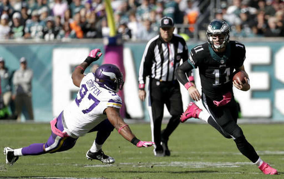 Philadelphia Eagles' Carson Wentz., right, runs for a first down past Minnesota Vikings' Everson Griffen during the first half of an NFL football game against the Minnesota Vikings, Sunday, Oct. 23, 2016, in Philadelphia. (AP Photo/Chris Szagola)