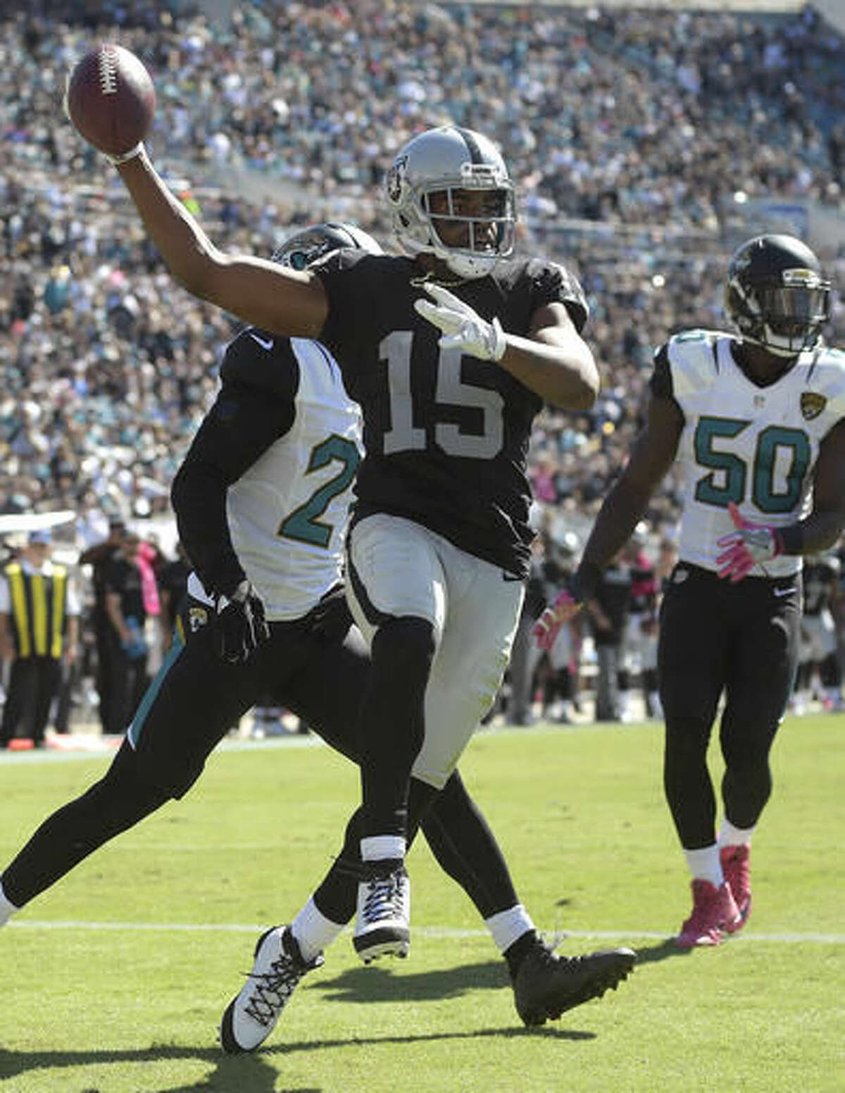Raiders wide receiver Michael Crabtree (15) celebrates his two-yard touchdown reception in front of Jacksonville Jaguars cornerback Prince Amukamara (21) and outside linebacker Telvin Smith (50) during the second quarter of an NFL football game Sunday, Oct. 23, 2016, in Jacksonville, Fla. (AP Photo/Phelan Ebenhack)