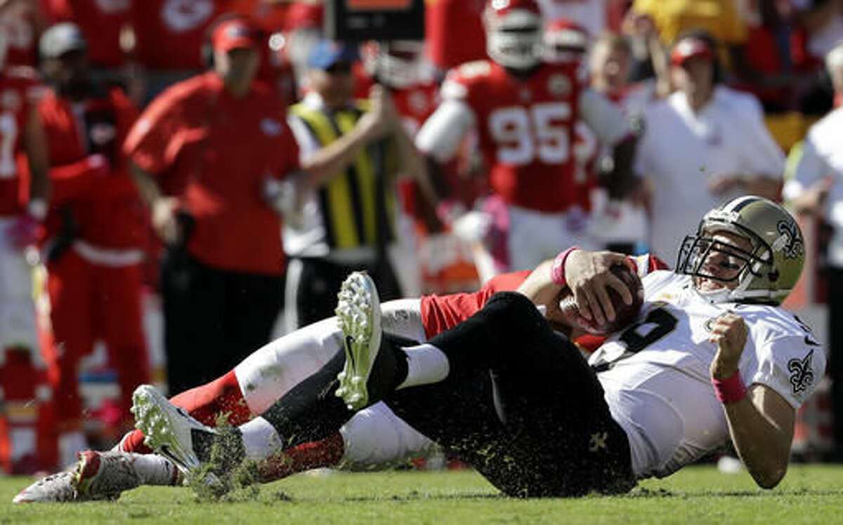New Orleans Saints quarterback Drew Brees (9) lands after being sacked by Kansas City Chiefs defensive back Daniel Sorensen, rear, during the first half of an NFL football game in Kansas City, Mo., Sunday, Oct. 23, 2016. (AP Photo/Jeff Roberson)