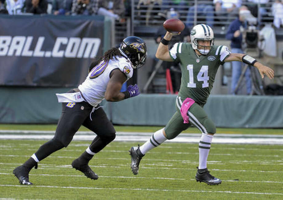 New York Jets quarterback Ryan Fitzpatrick (14) throws on the run as Baltimore Ravens outside linebacker Za'Darius Smith (90) pursues during the fourth quarter of an NFL football game, Sunday, Oct. 23, 2016, in East Rutherford, N.J. The Jets won 24-16. (AP Photo/Bill Kostroun)