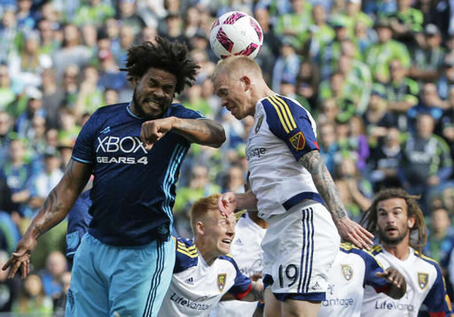 Seattle Sounders defender Roman Torres, left, and midfielder Luke Mulholland, right, go for a header in the first half of an MLS soccer match, Sunday, Oct. 23, 2016, in Seattle. (AP Photo/Ted S. Warren)