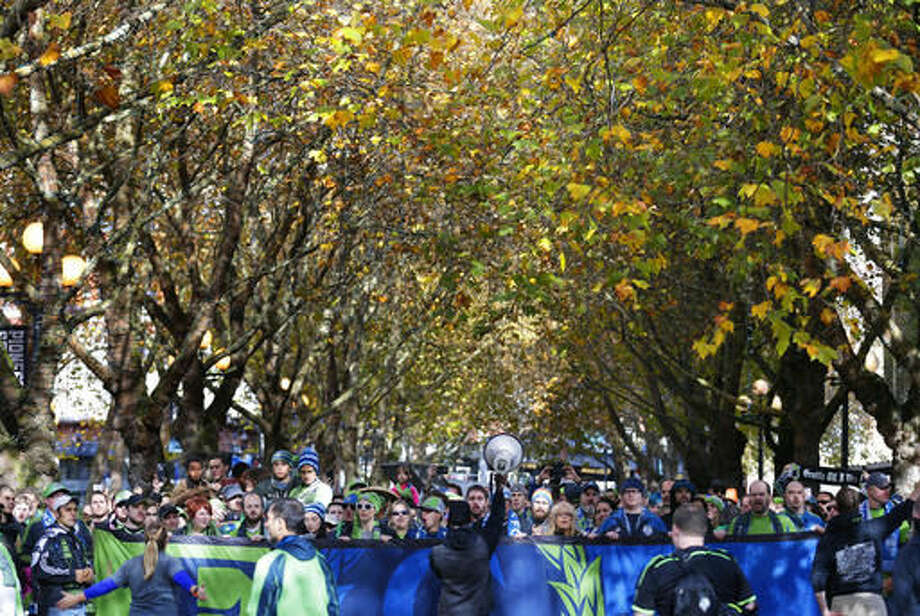 """Members of the Emerald City Supporters and other Seattle Sounders fans chant and sing during the traditional """"March to the Match,"""" Sunday, Oct. 23, 2016, before an MLS soccer match between the Sounders and Real Salt Lake in Seattle. (AP Photo/Ted S. Warren)"""