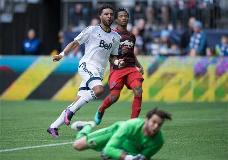 Vancouver Whitecaps' Giles Barnes, back left, celebrates his second goal against Portland Timbers' goalkeeper Jake Gleeson, bottom, as Alvas Powell, back right, watches during the first half of an MLS soccer game in Vancouver, British Columbia, on Sunday Oct. 23, 2016. (Darryl Dyck/The Canadian Press via AP)
