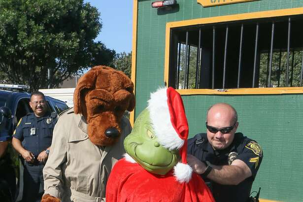 Cpl. William Feldtmose with the Live Oak Police Department arrests the Grinch with the help of McGruff the Crime Dog as police officers from Live Oak, Selma and Universal city kicked off the annual holiday safe shopping season with Operation Grinch 2016 in the Forum Shopping Center parking lot on Friday, Nov. 18, 2016.  MARVIN PFEIFFER/ mpfeiffer@express-news.net