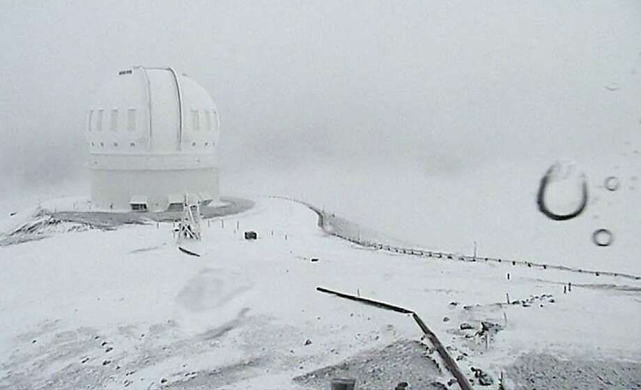 In this image made from webcam video provided by Canada-France-Hawaii Telescope, the CFHT telescope on the summit of Mauna Kea on Hawaii's Big Island is covered in snow on Thursday, Dec. 1, 2016. The National Weather Service in Honolulu has issued a winter storm warning for the summits of Hawaii's Big Island as wind and snow engulf the high peaks.  Photo: Canada-France-Hawaii Telescope, Associated Press