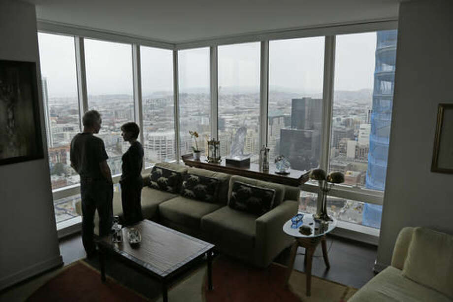 In this photo taken Monday, Oct. 3, 2016, Jerry Dodson and his wife Pat stand inside their home on the 42nd floor of the Millennium Tower in San Francisco. The 58-story tower has gained notoriety in recent weeks as the leaning tower of San Francisco. The Dodson's fear their investments are sinking along with the tower, and more immediately fear for their safety.