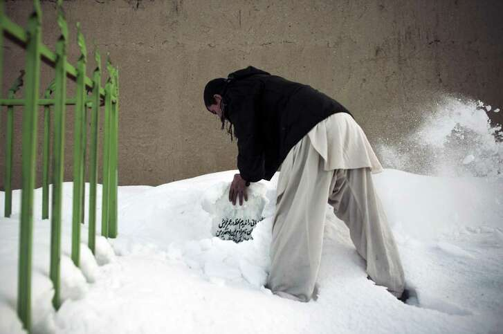 Mohammed Mansoori clears the grave of his brother, Qais, who died working while working for an American contractor, in Kabul, Afghanistan, Feb. 8, 2012. Last year, at least 430 employees of American contractors were reported killed in Afghanistan, more than the number of American soldiers killed. (Andrea Bruce/The New York Times)