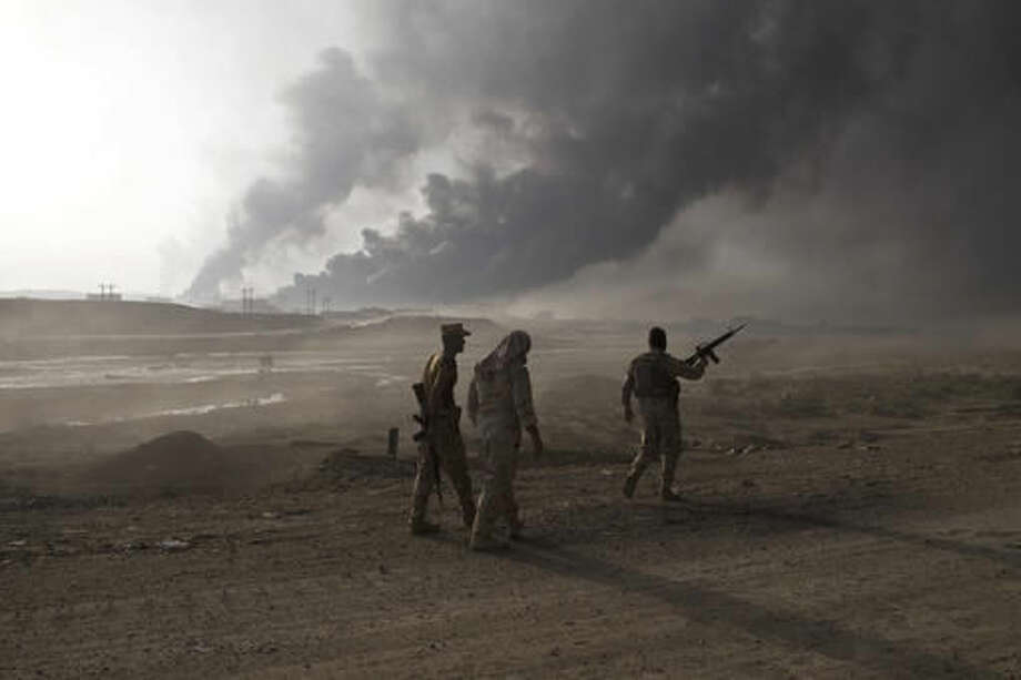 FILE - In this Wednesday, Oct. 19, 2016 file photo, Iraqi army soldiers man a checkpoint as oil wells burn on the outskirts of Qayyarah, Iraq. As the operation to retake Mosul enters its second month Iraqi forces are preparing for prolonged, grueling urban combat as they slow the tempo of their operation, advancing just a few hundred meters at a time. The individual tactics employed by IS mirror past fights with the group, but the sheer scale of IS defenses and counterattacks in Mosul has overwhelmed Iraq's military.(AP Photo/Marko Drobnjakovic, File)