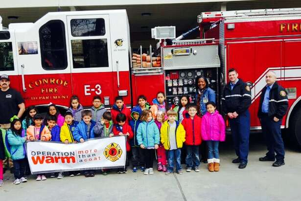 Conroe ISD elementary students are seen with Conroe Fire Department firefighters in January 2016 after receiving free winter coats. The Conroe Professional Firefighters Association is again participating in Operation Warm this month by providing brand new winter coats to B.B. Rice Elementary School students Monday. To donate, visithttps://give.operationwarm.org/events/conroe-firefighters-iaff-local-2731-operation-warm-fundraiser/e86652.