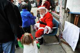 Santa greets children walking by on the street during the 33rd annual Troy Victorian Stroll on Sunday, Dec. 6, 2015, in Troy, N.Y.  (Paul Buckowski / Times Union)