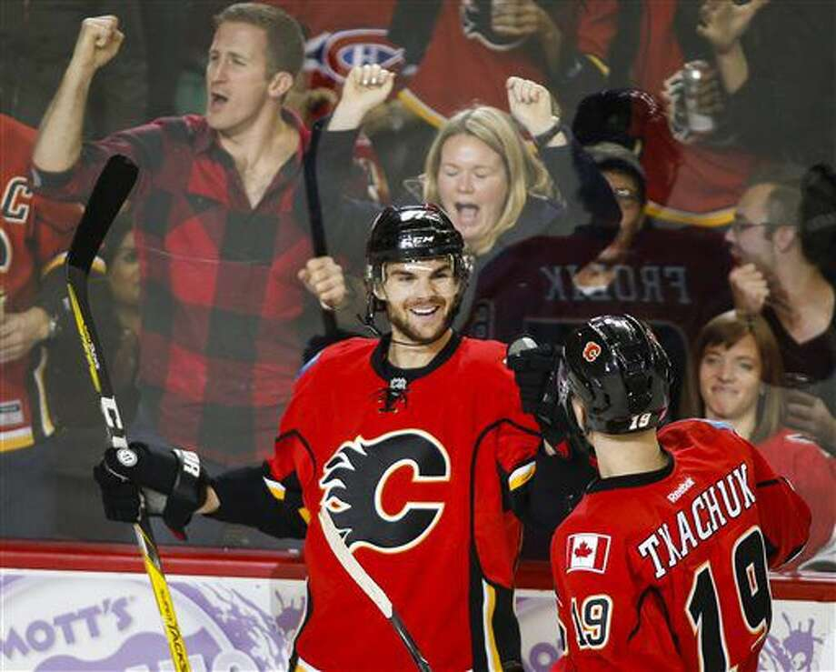 Calgary Flames' Michael Frolik, left, from the Czech Republic, celebrates his goal with teammate Matthew Tkachuk during the third period of an NHL hockey game against the Ottawa Senators on Friday, Oct. 28, 2016, in Calgary, Alberta. (Jeff McIntosh/The Canadian Press via AP)