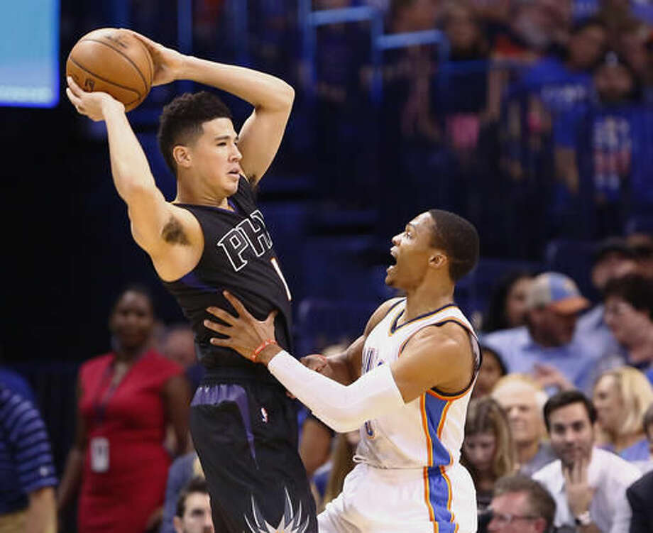 Phoenix Suns guard Devin Booker, left, looks to pass as Oklahoma City Thunder guard Russell Westbrook defends during the first quarter of an NBA basketball game in Oklahoma City, Friday, Oct. 28, 2016. (AP Photo/Alonzo Adams)