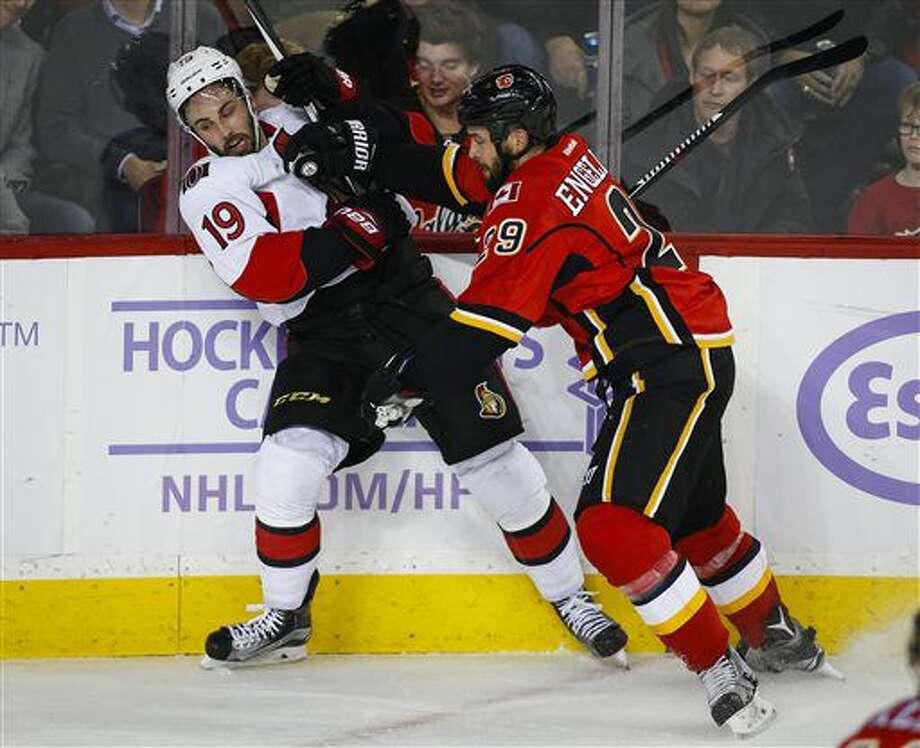 Ottawa Senators' Derick Brassard, left, tangles with Calgary Flames' Deryk Engelland during the second period of an NHL hockey game Friday, Oct. 28, 2016, in Calgary, Alberta. (Jeff McIntosh/The Canadian Press via AP)