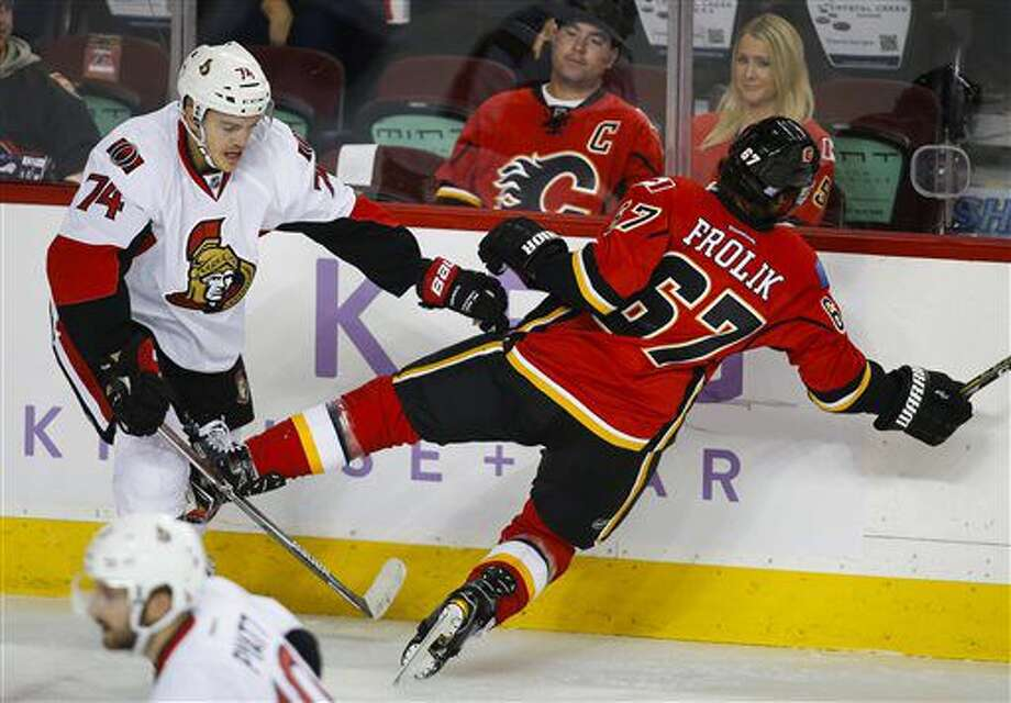 Ottawa Senators' Mark Borowiecki, left, knocks Calgary Flames' Michael Frolik, from the Czech Republic, to the ice during the first period of an NHL hockey game Friday, Oct. 28, 2016, in Calgary, Alberta. (Jeff McIntosh/The Canadian Press via AP)