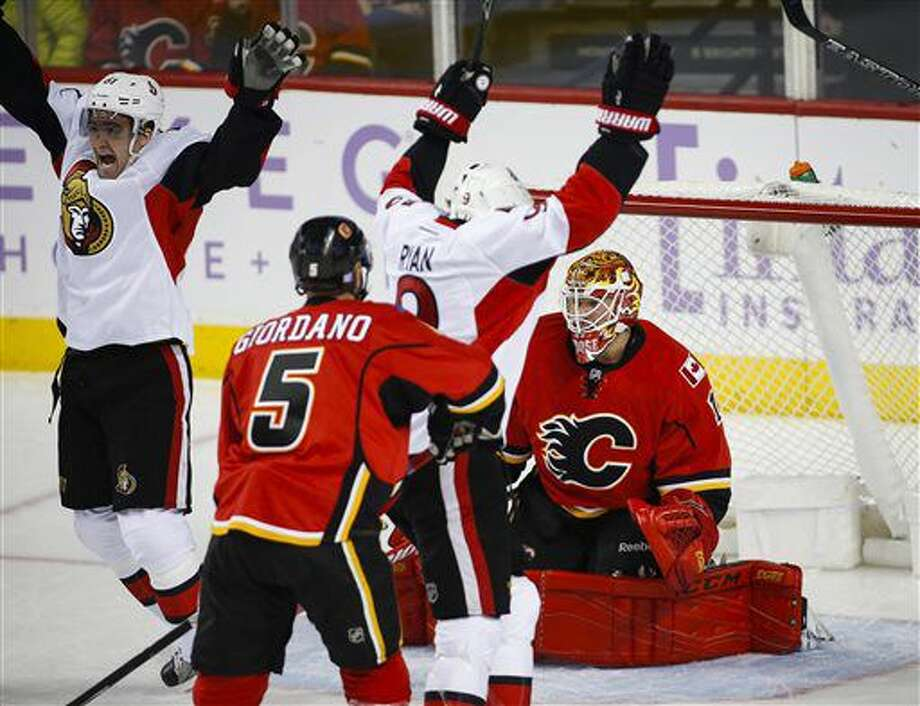 Ottawa Senators' Mark Stone, left, and Bobby Ryan celebrate the team's first goal as Calgary Flames goalie Brian Elliott kneels in front of the goal during the first period of an NHL hockey game Friday, Oct. 28, 2016, in Calgary, Alberta. (Jeff McIntosh/The Canadian Press via AP)