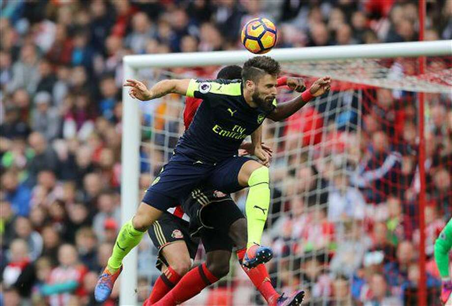 Arsenal's Olivier Giroud, front, heads the ball to score his side's third goal of the game during their English Premier League soccer match against Sunderland at the Stadium of Light, Sunderland, England, Saturday, Oct. 29, 2016. (Owen Humphreys/PA via AP)