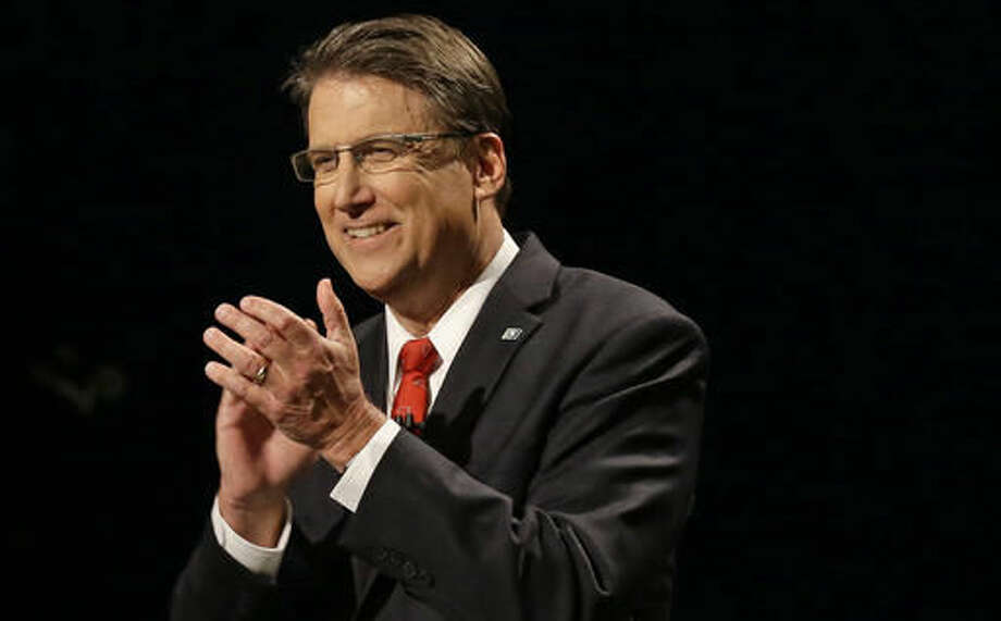 In this photo taken Tuesday, Oct. 11, 2016 North Carolina Republican Gov. Pat McCrory applauds during a debate with Democratic challenger Attorney General Roy Cooper, not shown, in a live televised debate in Research Triangle Park, N.C. The North Carolina governor's race is everything voters anticipated it would be: expensive attack ads and barbed debates before what's essentially a referendum on the state's recent rightward tilt under Republican rule, particularly the state law limiting protections for LGBT people _ known as House Bill 2. (AP Photo/Gerry Broome, File)