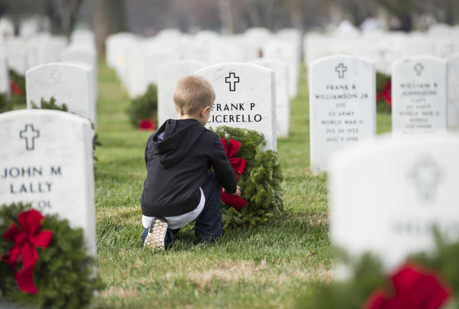 A young volunteer places a wreath during the 2015 National Wreaths Across America event at Arlington National Cemetery December 12, 2015 in Arlington, VA.  More than 50,000 volunteers helped to place remembrance wreaths on 230,000 gravestones at Arlington on Saturday.  AFP PHOTO/MOLLY RILEY / AFP / MOLLY RILEY        (Photo credit should read MOLLY RILEY/AFP/Getty Images) Photo: Getty Images