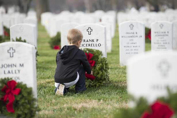 A young volunteer places a wreath during the 2015 National Wreaths Across America event at Arlington National Cemetery December 12, 2015 in Arlington, VA.  More than 50,000 volunteers helped to place remembrance wreaths on 230,000 gravestones at Arlington on Saturday.  AFP PHOTO/MOLLY RILEY / AFP / MOLLY RILEY        (Photo credit should read MOLLY RILEY/AFP/Getty Images)