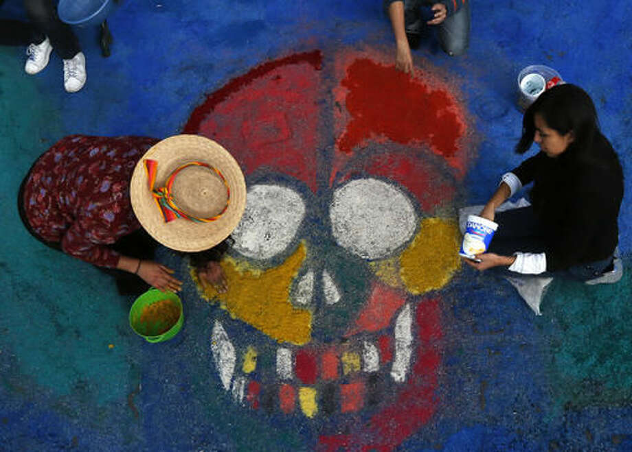 Residents create a sawdust representation of a skull during Day of the Dead festivities in Mexico City, Thursday, Oct. 27, 2016. The holiday honors the dead as friends and families gather in cemeteries to decorate their loved ones' graves and hold vigil through the night on Nov. 1 and 2. (AP Photo/Marco Ugarte)