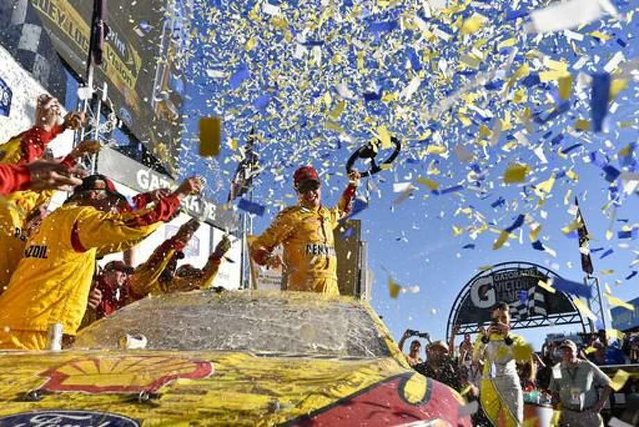 Joey Logano (22) celebrates after winning a NASCAR Sprint Cup Series auto race auto race at Talladega Superspeedway, Sunday, Oct. 23, 2016, in Talladega, Ala. (AP Photo/Matthew Bishop)