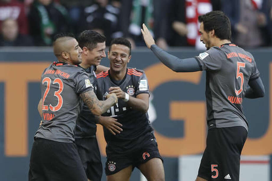 Bayern's Robert Lewandowski, second left, celebrates with team mates Arturo Vidal, left, Thiago, second right, and Mats Hummels, right, after scoring his side's third goal during the German Bundesliga soccer match between FC Augsburg and FC Bayern Munich in Augsburg, Germany, Saturday, Oct. 29, 2016. (AP Photo/Matthias Schrader)