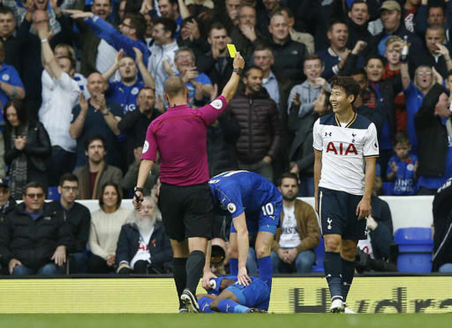 Tottenham Hotspur's Son Heung-min, right, is shown a yellow card by referee Robert Madley, during the English Premier League soccer match between Tottenham Hotspur and Leicester City at the White Hart Lane stadium in London in London, Saturday, Oct. 29, 2016. (AP Photo/Alastair Grant)