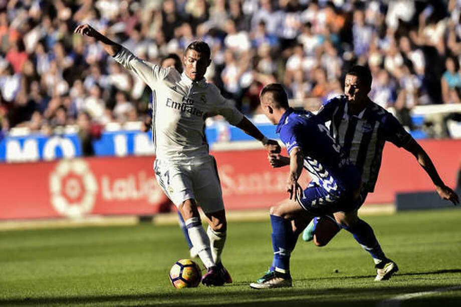 Real Madrid's Cristiano Ronaldo, left, duels for the ball with Deportivo Alaves's Raul Garcia during the Spanish La Liga soccer match between Real Madrid and Deportivo Alaves, at Mendizorroza stadium, in Vitoria, northern Spain, Saturday, Oct. 29, 2016. (AP Photo/Alvaro Barrie