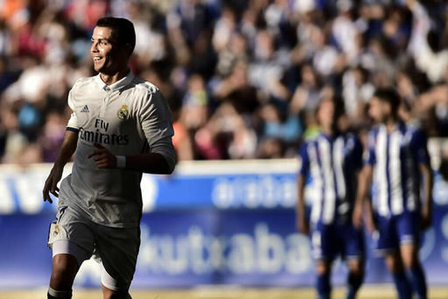 Real Madrid's Cristiano Ronaldo, left, smiles after scoring a second goal, during the Spanish La Liga soccer match between Real Madrid and Deportivo Alaves, at Mendizorroza stadium, in Vitoria, northern Spain, Saturday, Oct. 29, 2016. (AP Photo/Alvaro Barrientos)