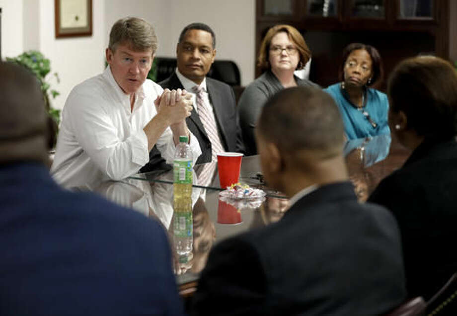 Missouri Democratic gubernatorial candidate Chris Koster, left, meets with healthcare professionals during a tour of Myrtle Hillard Davis Health Center, Thursday, Oct. 27, 2016, in St. Louis. Koster survived what few politicians have successfully weathered: a party change. Skeptics who knew him when he announced the switch before running for attorney general in 2008 called it political opportunism. His supporters say it's a demonstration of his ability to stick to his guns despite party pressure. (AP Photo/Jeff Roberson)