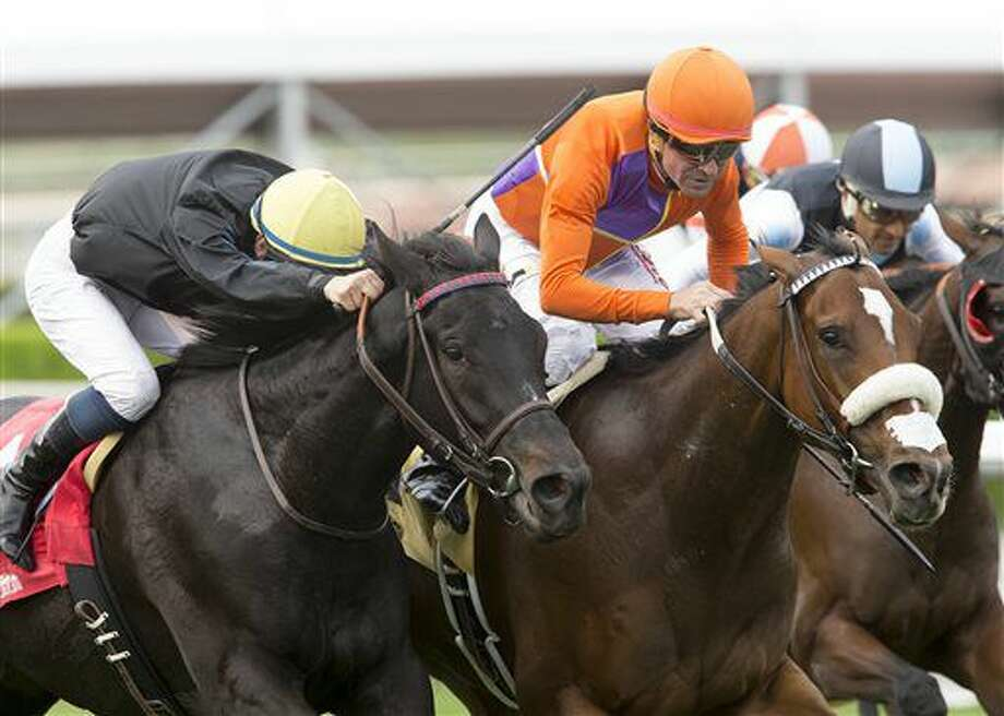 In this image provided by Benoit Photo, Spendthrift Farm's Cover Song and jockey Kent Desormeaux, right, overpower Danilovna (Flavien Prat), left, to win the Grade III, $100,000 Autumn Miss Stakes, Saturday, Oct. 29, 2016 at Santa Anita Park, Arcadia Calif. (Benoit Photo via AP)