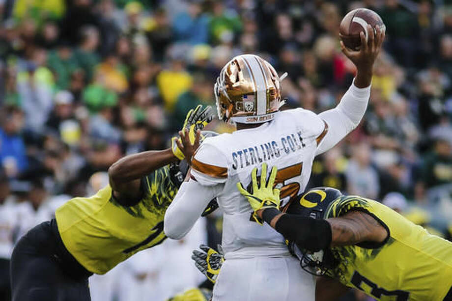 Oregon defensive lineman Justin Hollins, left, and linebacker Jonah Moi (3) sack Arizona State quarterback Dillon Sterling-Cole, in an NCAA college football game Saturday, Oct. 29, 2016 in Eugene, Ore. (AP Photo/Thomas Boyd)