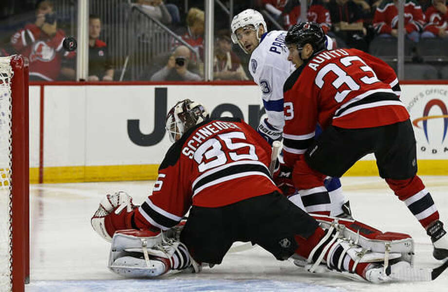 Tampa Bay Lightning center Cedric Paquette (13) watches his shot go over the net of New Jersey Devils goalie Cory Schneider (35) in front of defenseman Yohann Auvitu (33) during the first period of an NHL hockey game, Saturday, Oct. 29, 2016, in Newark, N.J. (AP Photo/Adam Hunger)