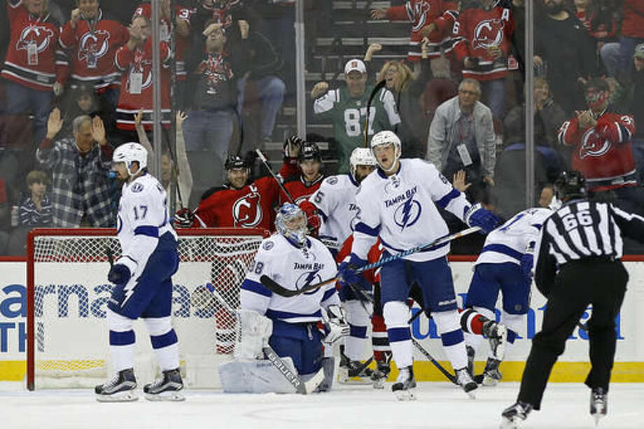 New Jersey Devils defenseman Damon Severson (28) celebrates scoring a goal on Tampa Bay Lightning goalie Andrei Vasilevskiy (88) with New Jersey Devils defenseman Andy Greene (6) during the first period of an NHL hockey game, Saturday, Oct. 29, 2016, in Newark, N.J. (AP Photo/Adam Hunger)