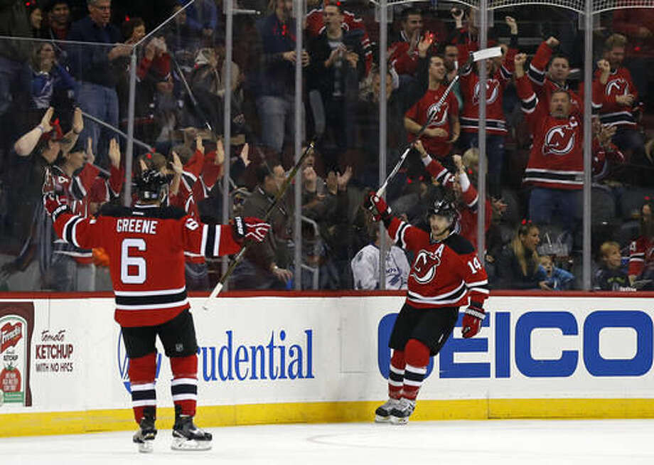 New Jersey Devils center Adam Henrique (14) celebrates scoring a goal with New Jersey Devils defenseman Andy Greene (6) during the first period of an NHL hockey game against the Tampa Bay Lightning, Saturday, Oct. 29, 2016, in Newark, N.J. (AP Photo/Adam Hunger)