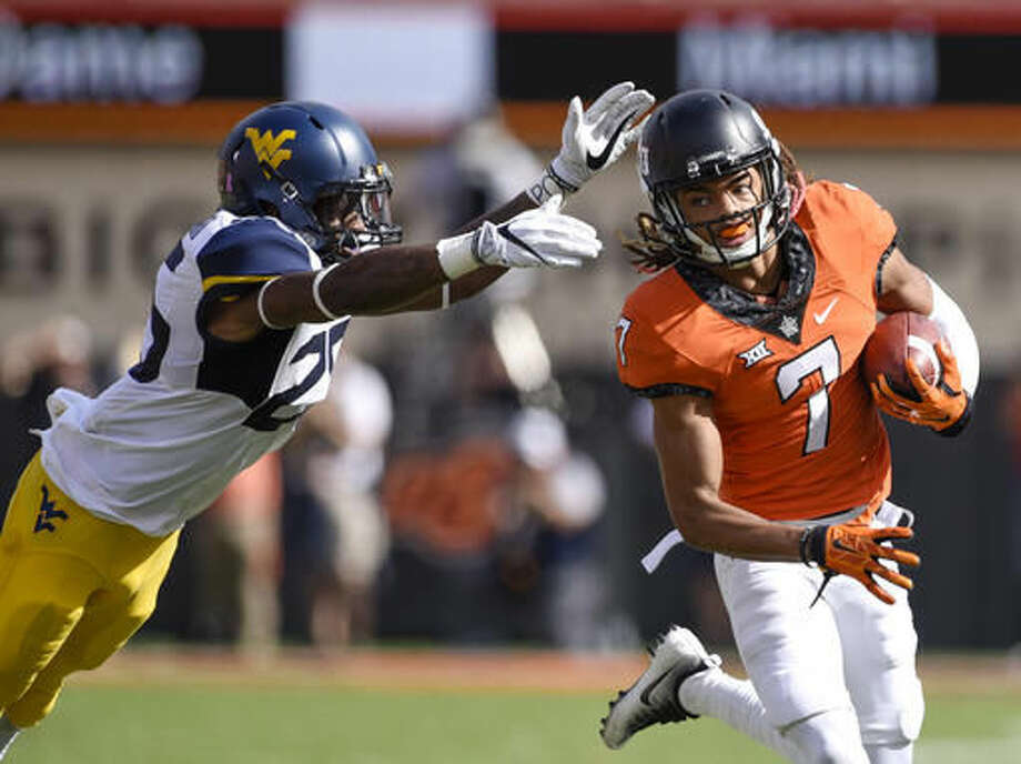 Oklahoma State's Ramon Richards (7) runs from West Virginia's Justin Crawford, as he returns an interception 59-yards during the second half of an NCAA college football game in Stillwater, Okla., Saturday, Oct. 29, 2016. Oklahoma State defeated West Virginia 37-20. (AP Photo/Brody Schmidt)