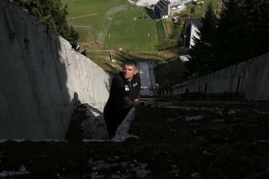 In this photo taken on Thursday, Sept. 15, 2016, Bosnian sports enthusiast Selver Merdanovic looks on from a destroyed ski jump facility at the mount Igman near Sarajevo. Sports enthusiasts and former athletes in Bosnia have taken it upon themselves to reclaim some of the glory Sarajevo savored as host of the 1984 Olympics - and in the process rekindled the flame of international cooperation. Since the country lacks the resources to rebuild the Olympic facilities that were destroyed in the deadly war that followed the breakup of Yugoslavia, volunteers bought tools, rolled up their sleeves and got to work. (AP Photo/Amel Emric)